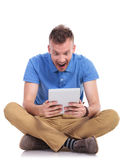 Seated young man shocked by his tablet Stock Photos