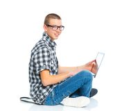 Seated young man using a laptop. Seated teenager using a laptop. Isolated on white background Royalty Free Stock Images