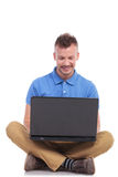 Seated young man works on laptop Stock Images