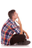 Seated young pensive man looking up Royalty Free Stock Photos