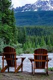 2 Seater Wood Adirondack Chairs buy a river in the canadain rockies. 2 Seater Wood Adirondack Chairs buy a river in the Canadian Rockies , lake Louise royalty free stock photos