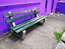 Seating against brick wall. Green wooden chair seat with bright purple wall royalty free stock image