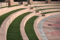 Seating at an amphitheater stage. Rows of curved concrete and grass seating at an outdoor amphitheater Stock Images