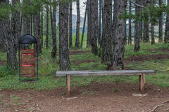 Seating bench in nature and a trash can 2 Royalty Free Stock Images