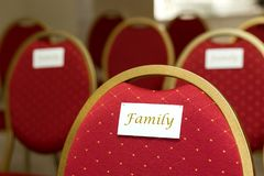 Seating chairs for guests at a wedding ceremony in the festive hall. Chairs upholstered in red cloth nameplate family.  stock photo
