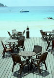 Seating by idyllic ocean. Scenic view of tables and empty seats on wooden patio decking by idyllic ocean, Redang Island, Malaysia Stock Photos