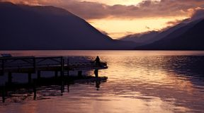 Seating on the Lake Dock. During Sunset. Cloudy Hills. Lake Crescent, Washington State. Washington State Photography Collection Royalty Free Stock Photo