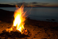 Seating near the romantic campfire on the beach watching sunset Royalty Free Stock Photography