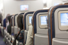 Seating space with multimedia screens economy class airplane cabin. Seating space with multimedia screens economy class airplane Stock Images