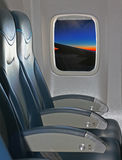 Seating and window inside an aircraft with view of wing and suns Stock Photography