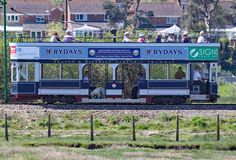 SEATON, ДЕВОН, АНГЛИЯ - 22-ОЕ МАЯ 2012: Голубой трамвай путешествует вдоль трамвая Seaton на своем пути к Colyford Оно бежит наря стоковые фотографии rf