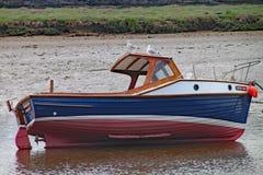 SEATON, ДЕВОН, АНГЛИЯ - 22-ОЕ МАЯ 2012: Небольшая рыбацкая лодка лежит на своей стороне во время отлива на лимане оси реки 2 чайк стоковые фото