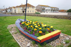 Seaton. Boat as plant pot in coastal town Seaton, Devon Royalty Free Stock Photo