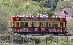 SEATON, DEVON, ENGELAND - MAG 22ND 2012: Een verfraaide rode tram reist langs het Seaton-tramspoor op zijn manier naar Colyford H royalty-vrije stock foto's