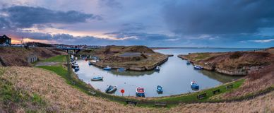 Seaton Sluice Harbour Panorama at sunset. Seaton Sluice is a village on the Northumberland coast, with a natural harbour formed by the Seaton Burn Stock Photos