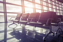 Seats in the airport waiting room at sunset.  Royalty Free Stock Photo
