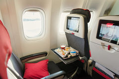 Seats on board of airplane. Cabin of economy class with screens stock photography