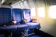 Seats in commercial aircraft cabin with sun light shining throug. H the windows Royalty Free Stock Photos