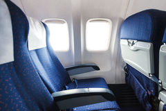 Seats in economy class section of airplane. Blue seats in economy class passenger section of airplane Royalty Free Stock Images