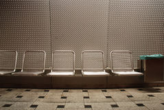 Seats in subway-station. Textured wall in the background, Munich, Germany Stock Image