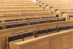 Seats and tables in auditory room at university. Cozy light lecture hall with wooden desks and comfortable chairs royalty free stock image