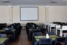 Seats and tables in dining room. Empty seats and tables in dining room with poster screen stock photo