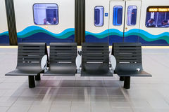 Seats in transit station. Seattle, WA, USA December 08, 2016: Seats in public transit station with Sound Transit Link Light Rail train in background Royalty Free Stock Photo