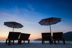 Seats and umbrella on beach under vivid colorful of sky at sunset timing. Located at south of Thailand royalty free stock photos