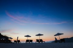 Seats and umbrella on beach under vivid colorful of sky at sunset timing. Located at south of Thailand stock photos