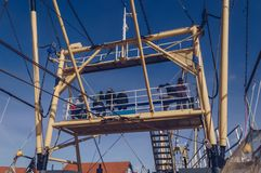 Seats on upper deck on fishing trawler. Oudeschild,Texel, The Netherlands, October 13, 2018: people sitting on the upper deck on fishing trawler stock photography