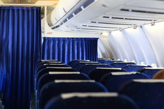 Seats and white panel inside airplane Stock Photography