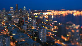 Seattle Cityscape Time Lapse Dusk Tilt Shift. V20. Seattle cityscape time lapse at dusk using a tilt shift lens with skyscrapers in focus and Elliott Bay out of stock video