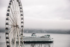 Seattle ferry passing by Great Wheel on foggy day Stock Images