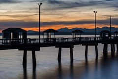 Seattle Fishing Pier at Sunset. The Peaks of the Olympic Mountains Rise over a Fishing Pier and the Puget sound in Seattle at Sunset Stock Photography