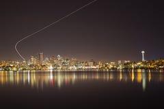 Seattle horisont vid natt med flygplanslingan Fotografering för Bildbyråer