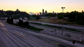 Seattle I-90 Traffic Time Lapse Sunset Zoom. V5. Zooming wide angle Seattle I-90 traffic time lapse during sunset with cityscape in background stock footage