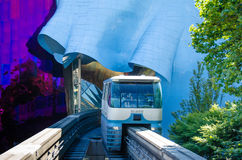 Seattle Monorail. The Seattle Center Monorail enters the 1962 World's Fair the site through the ultra-modern EMP Museum designed by architect Frank O. Gehry. The Stock Image