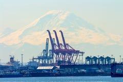 Seattle port med röda kranar och fartyg med Mt som är mer regnig i bacen Royaltyfri Fotografi
