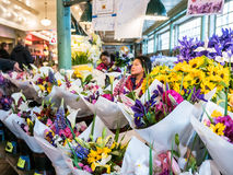 Seattle Public Market flower display with workers in background Stock Photos
