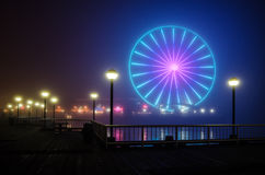 Seattle Great Wheel and Pier in Night Fog. On a very foggy night, the Great Wheel glows as seen from Waterfront Park in Seattle Stock Images