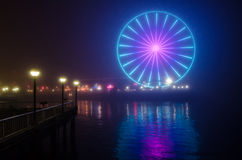 Seattle Great Wheel and Reflection in Night Fog - Horizontal. On a very foggy night, the Great Wheel glows as seen from Waterfront Park in Seattle Royalty Free Stock Image