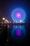 Seattle Great Wheel and Reflection in Night Fog - Vertical. On a very foggy night, the Great Wheel glows as seen from Waterfront Park in Seattle Royalty Free Stock Image