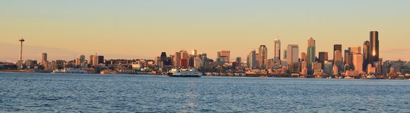Seattle skyline. At sunset with ferry crossing water toward dock Stock Photo