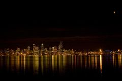 Seattle skyline with eclipse. View of the Seattle skyline at night with the moon almost at full lunar eclipse Stock Photography