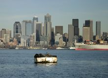 Seattle skyline and harbor. A view of downtown Seattle from a boat on Elliott Bay. In the foreground, a buoy has several seals lounging around stock photo