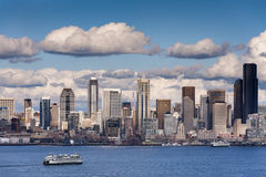 Seattle Skyline. A lovely spring day along the Seattle, Washington waterfront. This view across Elliott Bay pictures puffy clouds and ferryboats with modern Stock Photography