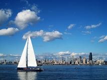 Seattle Skyline with Sailboat. Seattle Skyline with a large sailboat in the foreground with the sails extending above the hoirzon. The Seattle Space Needle is royalty free stock photo