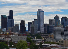 Seattle Skyline with Skyscrapers. During the day with a sky filled with white clouds. Green trees in the foreground Royalty Free Stock Photography