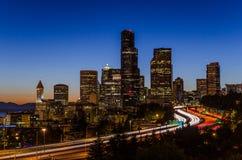 Seattle-Skyline und -autobahn an der Dämmerung Stockbild