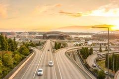 Seattle-Skyline und zwischenstaatliche Autobahnen laufen mit Elliott Bay und dem Ufergegendhintergrund in der Sonnenuntergangzeit Stockbilder